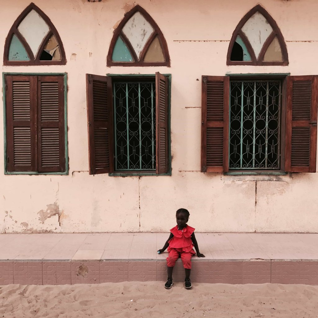Little girl sitting in front of a house in Saint Louis Senegal Photo taken in December 2016