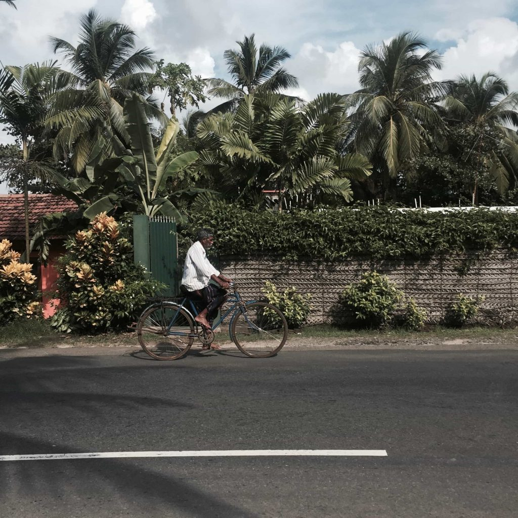 Man cycling by the streets of Bentota in Sri Lanka Photo taken in December 2015