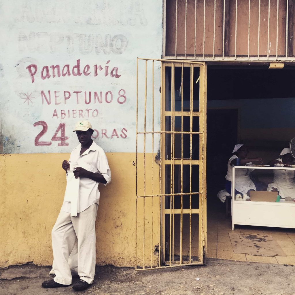 Cuban man in front of shop in Havana