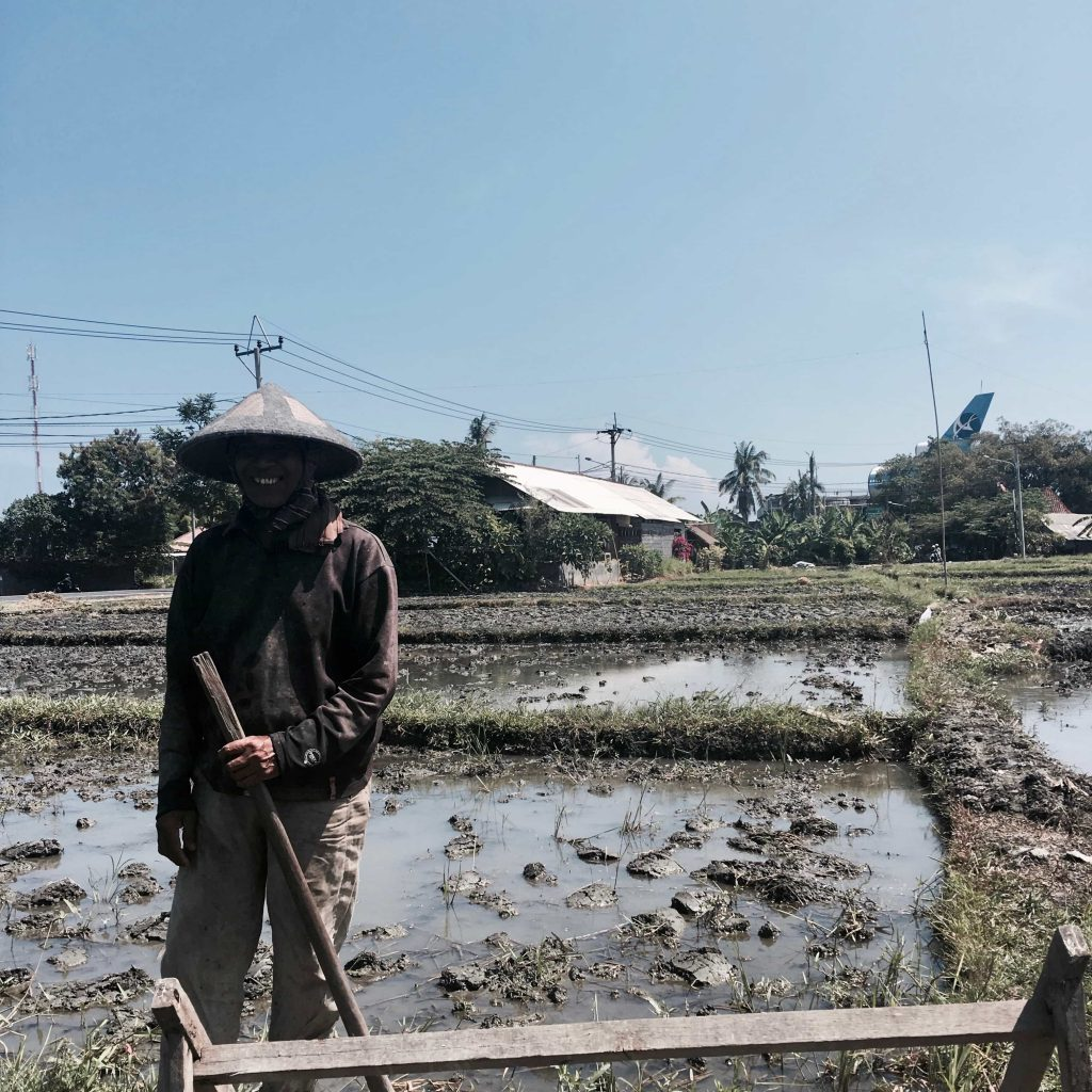 Rice field farmer smiling while at work Taken in Bali in May 2016