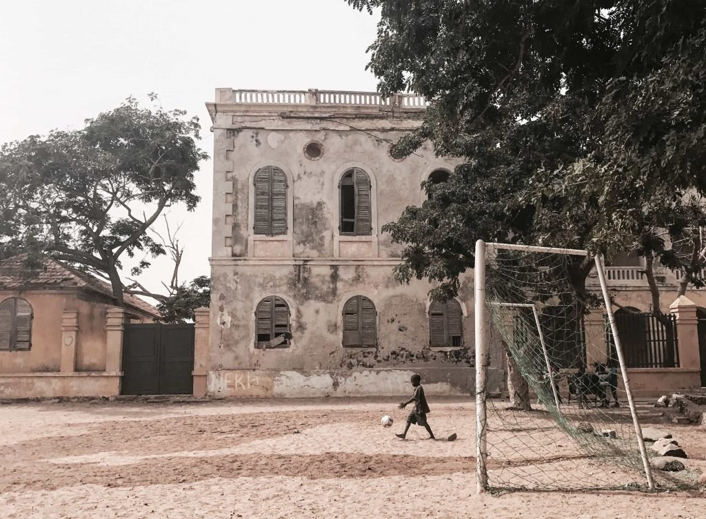 55. Boy playing football in Goree Island